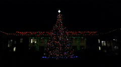 An outdoor Christmas tree in front of a large house trimmed with lights at night - stock footage
