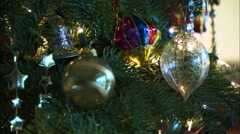 Rack focus on Christmas tree ornaments among green branches Stock Footage
