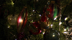 Close-up of a woman's hand placing a Christmas ornament among others already on Stock Footage