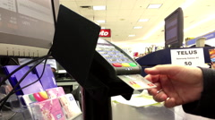 Woman paying credit card to buy sd card at check out counter Stock Footage