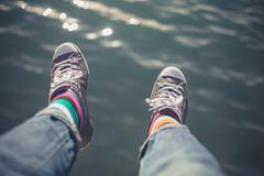Man dangling feet over water - stock photo