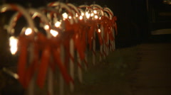 Left pan over row of tall candy canes tied with red bows and strung with Stock Footage
