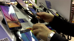 Woman trying display cellphone inside London Drugs store Stock Footage