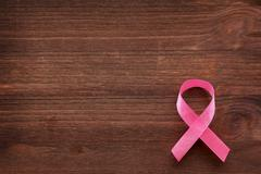 Pink ribbon - symbol of breast cancer awareness. Wooden background. Good as b Stock Photos