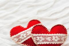 White fabric background with ruche.Two felt hearts with laces, symbol of love - stock photo