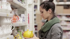 Young woman chooses shelves in the supermarket Stock Footage