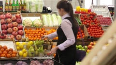 Woman selecting fruit at market and adds to cart, rear view Stock Footage