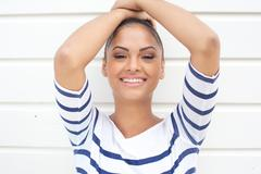 Young latin american woman smiling on white background - stock photo