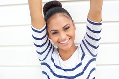 Beautiful young woman smiling with arms raised - stock photo