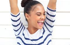 Portrait of a happy latin american smiling with arms raised - stock photo