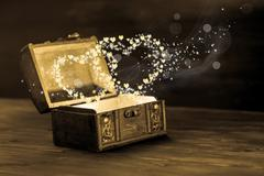 beautiful concept of vintage chest with light heart miracle on wooden backgro - stock photo