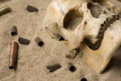 Skull lying in the sand, scattered rifle and pistol cartridges. concept of war Stock Photos