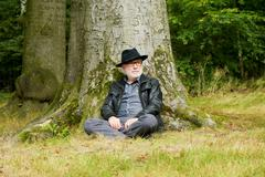 Wise old man sitting under tree in the forest - stock photo