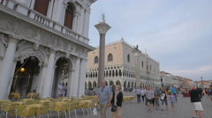 Tourists walking by Piazza San Marco's columns and palaces in Venice Stock Footage