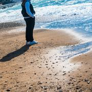 Woman staying near water on the beach - stock photo