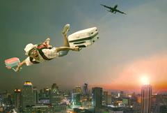 younger man flying mid air with belonging luggage and passenger plane over be - stock photo