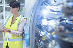 Stock Photo of Worker with digital tablet leaning on machinery in factory