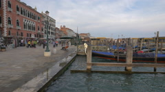 Moored gondolas in a station, people walking on Riva degli Schiavoni in Venice Stock Footage