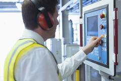 Worker with ear protectors at control panel in machinery - stock photo