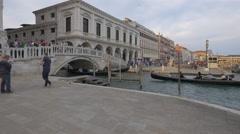 People on a bridge over Rio de palazzo and gondolas sailing under it in Venice Stock Footage