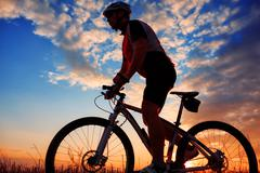Man Cyclist with bike on sunset Stock Photos