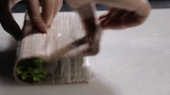 Cooking sushi rolls in the studio. forming into a square roll mat Stock Footage