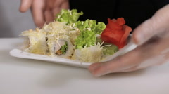 Chef flips a plate of sushi rolls. gloved hand of the master Stock Footage