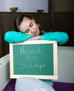 beautiful slim woman in a tracksuit with chalkboard - need to sleep - stock photo