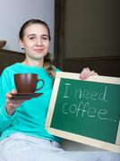 beautiful slim woman in a tracksuit with chalkboard - i need coffee - stock photo