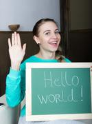 beautiful slim woman in a tracksuit with chalkboard - hello world - stock photo