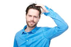 Confused male individual with hand in hair - stock photo