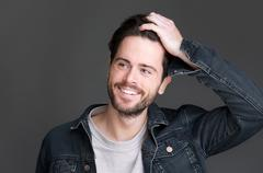 Portrait of an attractive young man smiling with hand in hair Stock Photos
