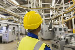 Stock Photo of Worker in hard-hat watching printing press conveyor belts and machinery in