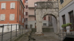 View of an old arch surrounded by buildings in Trieste Stock Footage