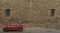 Small red car parked near a stone wall in Trieste Stock Footage