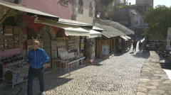 View of a man and a teenager walking by souvenir shops in Mostar Stock Footage