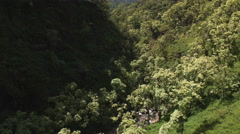 Flying up a narrow valley on Molokai, rotating above a waterfall. Shot in 2010. Stock Footage
