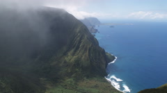 Over wooded hills to wide view of the Molokai coastline. Shot in 2010. Stock Footage