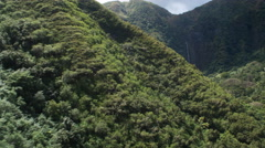 Around a tree-covered hillside to a close view of waterfalls, Molokai. Shot in Stock Footage