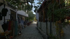 Stock Video Footage of Outdoor restaurant and souvenir shops on a narrow street in Mostar