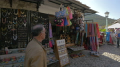 Stock Video Footage of People walking by and buying from souvenir shops in Mostar