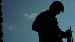 Silhouette of a man drills a wood Stock Footage