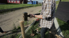 Man hammers in stake in the ground close-up Stock Footage