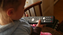 Little kid girl play with buttons of TV remote controller Stock Footage