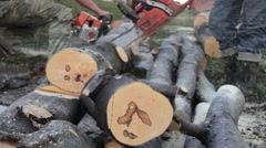 Three men cut from logs using a chainsaw. The pieces are measured 24 Stock Footage