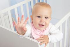 Portrait of a cute baby waving hello and smiling from crib - stock photo