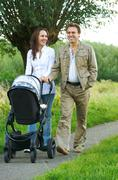 Mother and father walking outdoors with baby stroller - stock photo