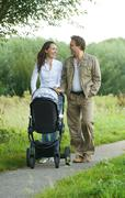 Happy mother and father pushing baby pram outdoors - stock photo