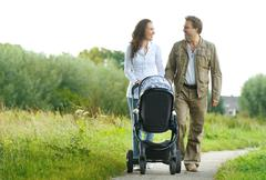 Happy man and woman walking with baby pram outdoors - stock photo