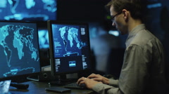 IT professional in glasses is working on computer in cyber security center - stock footage